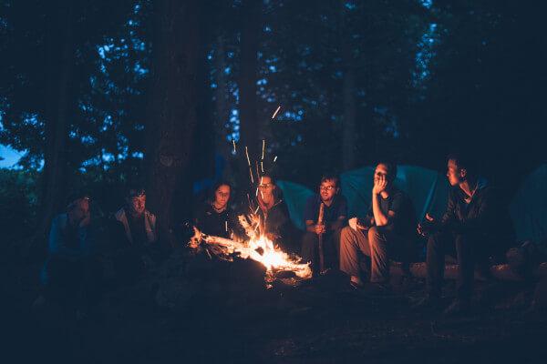 Company Retreat participants sitting around campfire